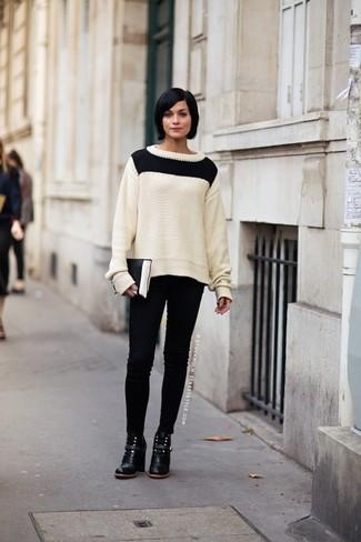 Come indossare: maglione a trecce bianco e nero, jeans aderenti neri, stivaletti in pelle neri, pochette in pelle nera e bianca