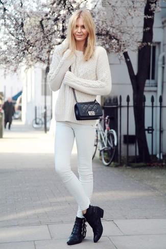 Punta su un maglione a trecce bianco e jeans aderenti bianchi per un look raffinato ma semplice. Sfodera il gusto per le calzature di lusso e opta per un paio di stivaletti in pelle neri.
