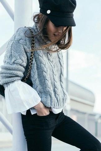 Come indossare: maglione a trecce lavorato a maglia grigio, camicetta manica lunga con volant bianca, jeans aderenti neri, borsa a tracolla in pelle scamosciata nera