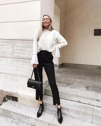 Come indossare: maglione a trecce bianco, camicetta manica lunga con volant bianca, pantaloni stretti in fondo neri, stivaletti in pelle neri