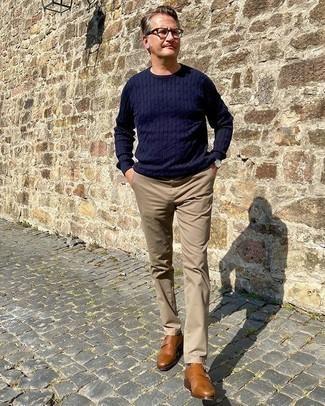 Moda uomo anni 50: Potresti combinare un maglione a trecce blu scuro con chino marrone chiaro per un look spensierato e alla moda. Abbellisci questo completo con un paio di scarpe double monk in pelle terracotta.