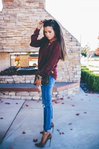 Come indossare e abbinare: maglione a trecce bordeaux, jeans strappati blu, décolleté in pelle marrone scuro, pochette in pelle stampata marrone scuro
