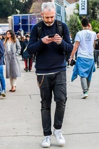 Come indossare e abbinare jeans strappati grigio scuro: Metti un maglione a trecce blu scuro e jeans strappati grigio scuro per un outfit rilassato ma alla moda. Calza un paio di sneakers basse in pelle bianche per dare un tocco classico al completo.