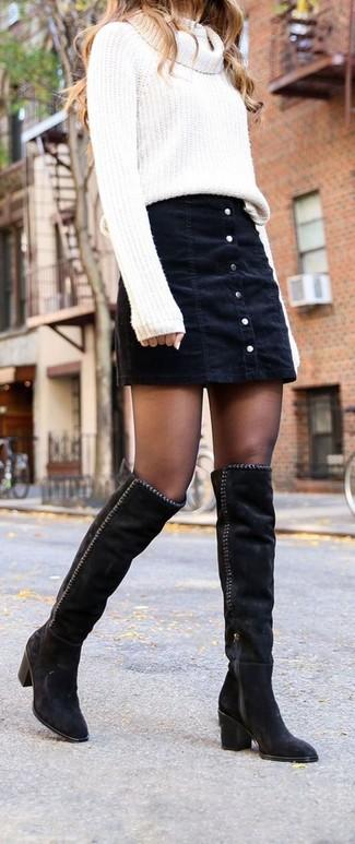 Come indossare: maglione con scollo a cappuccio bianco, gonna con bottoni di jeans nera, stivali sopra il ginocchio in pelle scamosciata neri