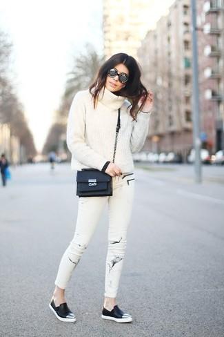 Come indossare: maglione con scollo a cappuccio bianco, jeans aderenti stampati bianchi, sneakers senza lacci in pelle nere, borsa a tracolla in pelle nera