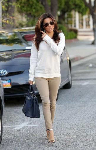 Come indossare e abbinare: maglione con scollo a v bianco, jeans aderenti beige, sandali con tacco in pelle argento, borsa shopping in pelle nera