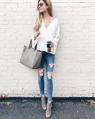 Come indossare e abbinare: maglione con scollo a v bianco, jeans aderenti strappati blu, stivaletti in pelle tagliati grigi, borsa shopping in pelle grigia