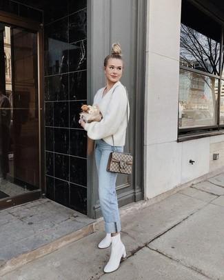 Come indossare e abbinare: maglione con scollo a v bianco, jeans azzurri, stivaletti in pelle bianchi, cartella di tela stampata beige