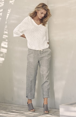 Come indossare: maglione con scollo a v bianco, pantaloni larghi di lino grigi, sandali con zeppa in pelle grigi