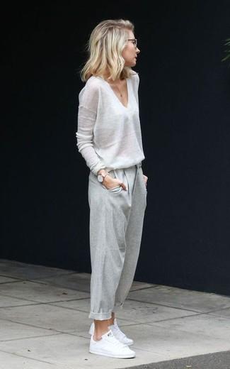 Come indossare e abbinare: maglione con scollo a v bianco, pantaloni stretti in fondo grigi, sneakers basse bianche, orologio dorato