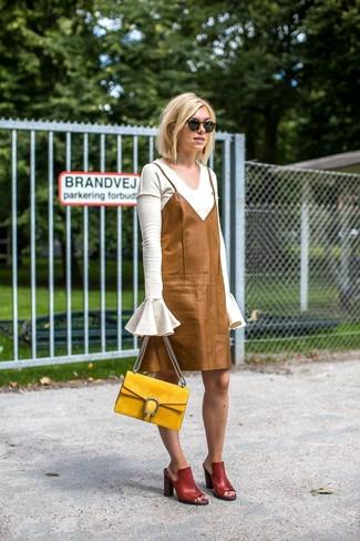 Come indossare e abbinare: maglione con scollo a v bianco, sottoveste in pelle marrone chiaro, sabot in pelle bordeaux, cartella in pelle scamosciata gialla