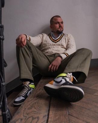 Trend da uomo 2021: Scegli un maglione con scollo a v beige e chino verde oliva per un pranzo domenicale con gli amici. Per distinguerti dagli altri, calza un paio di sneakers alte in pelle bianche e nere.