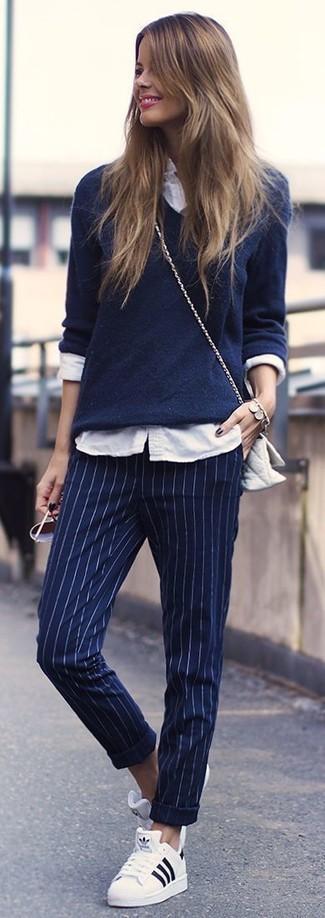 Come indossare e abbinare pantaloni eleganti a righe verticali blu scuro: Scegli un maglione con scollo a v blu scuro e pantaloni eleganti a righe verticali blu scuro per un look raffinato per il tempo libero. Non vuoi calcare troppo la mano con le scarpe? Indossa un paio di sneakers basse bianche per la giornata.