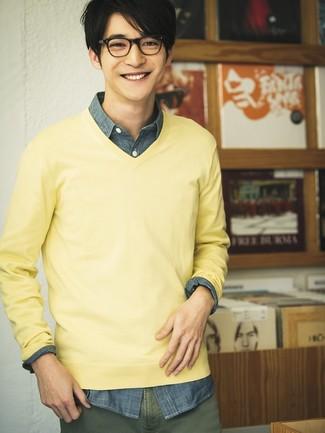 Come indossare e abbinare: maglione con scollo a v giallo, camicia a maniche lunghe in chambray blu scuro, chino verde oliva