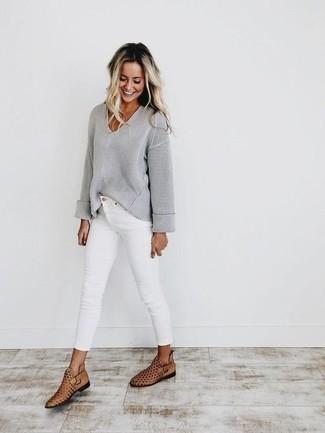 Trend da donna 2020: Abbina un maglione con scollo a v grigio con jeans aderenti bianchi per un pranzo domenicale con gli amici. Stivaletti in pelle tagliati marrone chiaro sono una valida scelta per completare il look.
