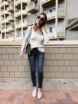 Come indossare: maglione con scollo a v beige, jeans aderenti strappati neri, mocassini eleganti in pelle scamosciata beige, borsa a tracolla in pelle grigia