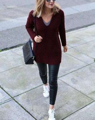Come indossare e abbinare: maglione con scollo a v bordeaux, t-shirt con scollo a v grigia, jeans aderenti in pelle neri, sneakers basse in pelle bianche