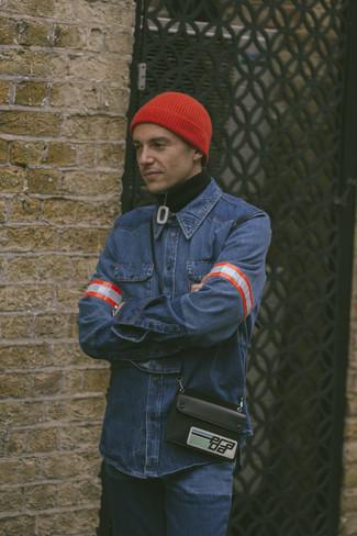 Come indossare e abbinare: maglione con zip nero, camicia di jeans blu, jeans blu, berretto rossa