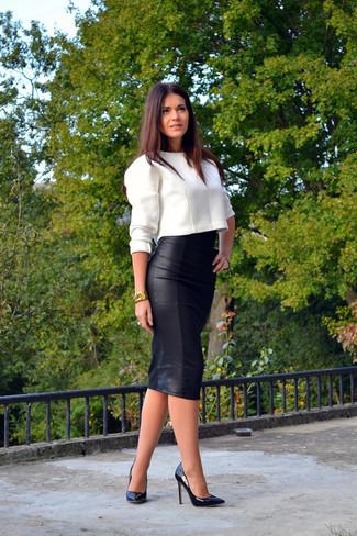 Sfoggia un look raffinato e disinvolto in un maglione corto bianco e una gonna longuette in pelle nera. Décolleté in pelle neri daranno lucentezza a un look discreto.
