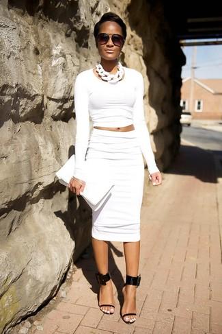 Come indossare: maglione corto bianco, gonna a tubino bianca, sandali con tacco in pelle neri, pochette in pelle bianca