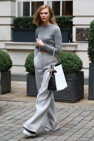 Come indossare: maglione corto grigio, pantaloni larghi di lana grigi, mocassini con zeppa in pelle neri e bianchi, borsa shopping in pelle bianca e nera