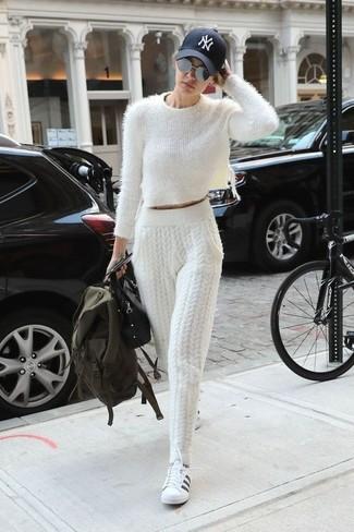 Come indossare: maglione corto morbido bianco, pantaloni sportivi lavorati a maglia bianchi, sneakers basse in pelle bianche e nere, cartella in pelle nera