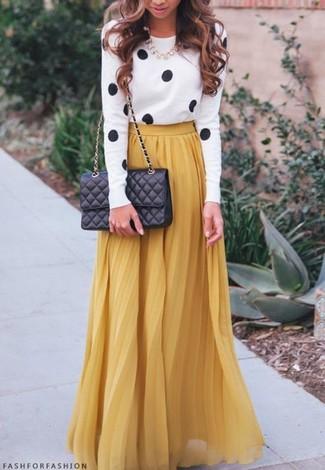 Questa combinazione di un maglione girocollo a pois bianco e nero e una gonna lunga a pieghe senape è perfetta per il tempo libero.