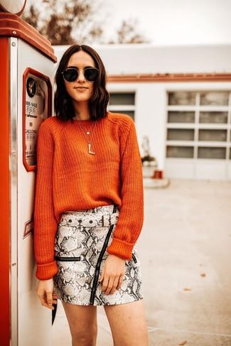 Come indossare e abbinare: maglione girocollo arancione, minigonna in pelle con stampa serpente grigia, occhiali da sole neri e dorati, collana con ciondolo dorata