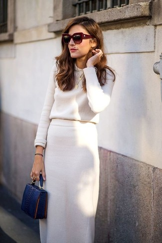 Come indossare: maglione girocollo beige, gonna longuette beige, pochette in pelle con stampa serpente blu scuro, occhiali da sole bordeaux