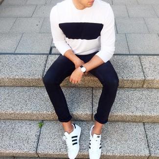Come indossare e abbinare: maglione girocollo bianco e nero, jeans aderenti neri, sneakers basse in pelle bianche e nere, orologio in pelle nero