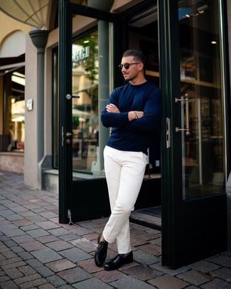 Come indossare e abbinare: maglione girocollo blu scuro, chino bianchi, mocassini eleganti in pelle neri, occhiali da sole neri