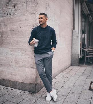Come indossare e abbinare: maglione girocollo stampato blu scuro, pantaloni eleganti grigi, sneakers basse bianche, orologio argento