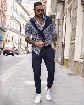 Come indossare e abbinare: maglione girocollo blu scuro, camicia a maniche lunghe a fiori blu scuro e bianca, chino blu scuro, sneakers basse in pelle bianche