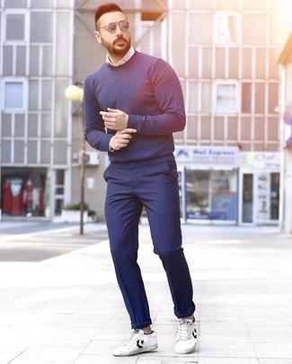 Come indossare e abbinare: maglione girocollo blu scuro, camicia a maniche lunghe stampata bianca e blu, chino blu scuro, sneakers basse in pelle bianche e nere