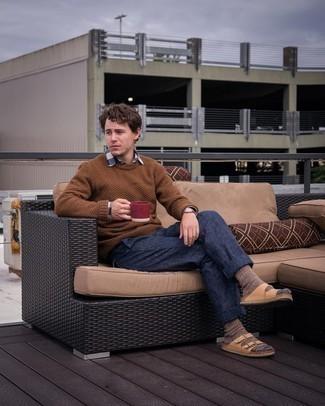Moda uomo anni 20: Per creare un adatto a un pranzo con gli amici nel weekend metti un maglione girocollo marrone e chino blu scuro. Per distinguerti dagli altri, calza un paio di sandali in pelle marrone chiaro.