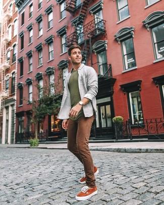 Come indossare e abbinare: maglione girocollo verde oliva, camicia a maniche lunghe grigia, jeans aderenti marroni, sneakers basse in pelle scamosciata terracotta