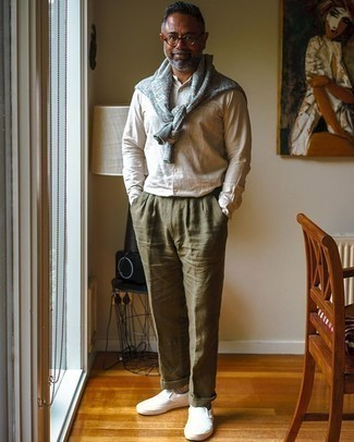 Trend da uomo 2020 in modo smart-casual: Vestiti con un maglione girocollo grigio e pantaloni eleganti di lino verde oliva per un look elegante e di classe. Per un look più rilassato, scegli un paio di sneakers senza lacci di tela bianche.