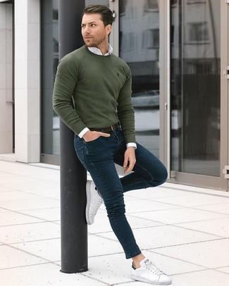 Come indossare e abbinare: maglione girocollo verde oliva, camicia elegante bianca, jeans aderenti blu scuro, sneakers basse in pelle bianche