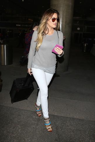 Come indossare e abbinare: maglione girocollo grigio, canotta grigia, jeans aderenti bianchi, sandali con tacco in pelle decorati multicolori