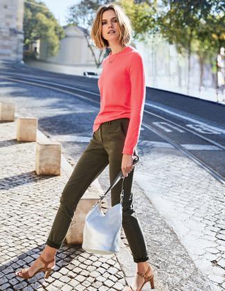 Come indossare e abbinare: maglione girocollo fucsia, jeans aderenti verde oliva, sandali con tacco in pelle marroni, borsa a secchiello in pelle argento