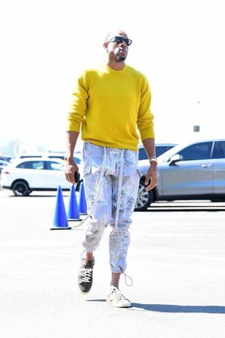 Come indossare e abbinare: maglione girocollo giallo, pantaloni cargo stampati viola chiaro, sneakers basse in pelle scamosciata beige, occhiali da sole neri
