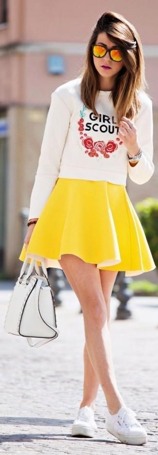 Come indossare e abbinare: maglione girocollo stampato bianco, gonna a pieghe gialla, scarpe da ginnastica di tela bianche, cartella in pelle bianca