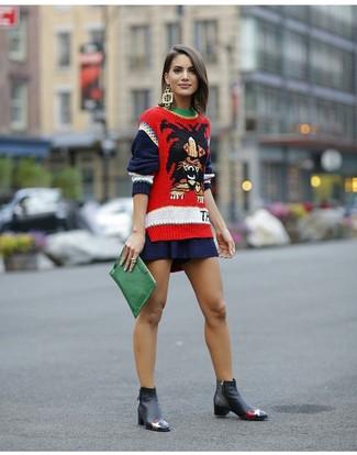 Come indossare: maglione girocollo stampato rosso, gonna a pieghe blu scuro, stivali chelsea in pelle neri, pochette in pelle verde