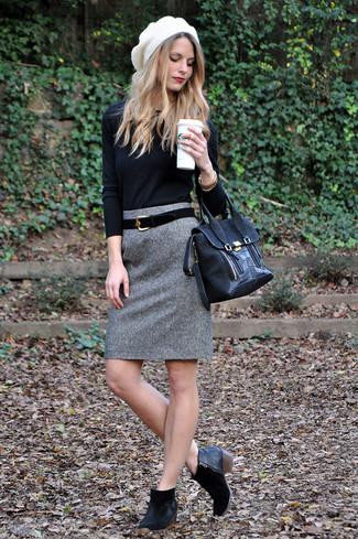 Come indossare: maglione girocollo nero, gonna a tubino di lana grigia, stivaletti in pelle scamosciata neri, cartella in pelle scamosciata nera