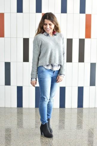 Come indossare: maglione girocollo grigio, camicia elegante scozzese bianca e blu scuro, jeans aderenti strappati azzurri, stivaletti in pelle neri