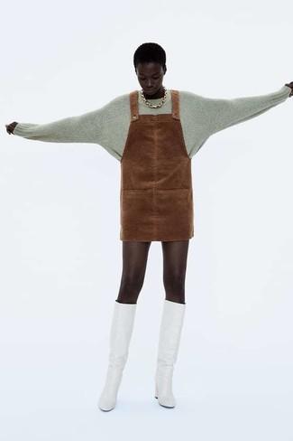 Come indossare: maglione girocollo grigio, scamiciato in pelle scamosciata marrone, stivali al ginocchio in pelle bianchi, collana dorata