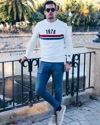 Come indossare e abbinare: maglione girocollo stampato bianco, jeans aderenti blu, sneakers basse in pelle grigie, occhiali da sole blu scuro
