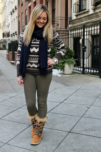 Come indossare e abbinare: maglione girocollo con motivo fair isle marrone, jeans aderenti verde oliva, stivali da neve marrone chiaro, sciarpa blu scuro