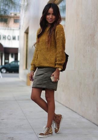 Come indossare e abbinare: maglione girocollo morbido marrone, minigonna verde oliva, sneakers alte leopardate marrone chiaro, orologio dorato