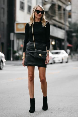 Questo abbinamento di un maglione girocollo nero e una minigonna in pelle nera attira l'attenzione per le ragioni giuste. Indossa un paio di stivaletti in pelle scamosciata neri per un tocco virile.